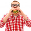 Funny man in glasses eating hamburger — Stock Photo