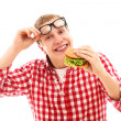 Funny man in glasses eating hamburger — Stock Photo #16688279