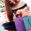 Attractive woman checking shopping bags at home — Stok fotoğraf