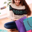 Attractive woman checking shopping bags at home — Stock Photo #16689841