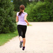 Young and attractive girl running in the park — Stock Photo