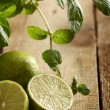 Fresh sliced lime with mint on a wooden surface - Stock Photo