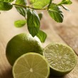 Fresh sliced lime with mint on a wooden surface — Stock Photo #16851865