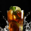 Cold tea with lemon and mint in water splashing — Stock fotografie
