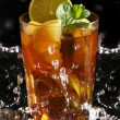 Cold tea with lemon and mint in water splashing - Stock Photo