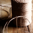 Spool of thread and needle over wooden surface — Stock Photo