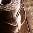 Spool of thread and needle over wooden surface - Lizenzfreies Foto