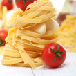 Dry pasta, cherry tomatoes and garlic close up - Stock Photo