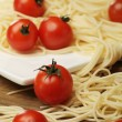 Tomatoes with spaghetti on square plate — Stock Photo