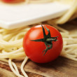 Tomatoes with spaghetti on square plate - Стоковая фотография