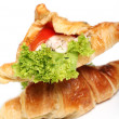 Delicious croissants with salad and tomato inside - Stock Photo