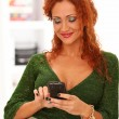 Beautiful redhead woman using cellphone — Stockfoto