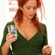Beautiful redhead woman drinking medicine — Stock Photo