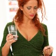 Royalty-Free Stock Photo: Beautiful redhead woman drinking medicine