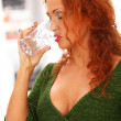 Beautiful redhead woman drinking water — Stock Photo