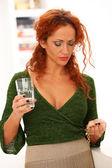 Beautiful redhead woman drinking medicine — Stock Photo