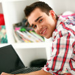Handsome man working with laptop at home - 图库照片