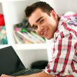 Handsome man working with laptop at home - Foto de Stock
