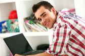 Pohledný muž pracující s přenosným počítačem doma — Stock fotografie