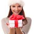 Girl smiling in christmas hat and holding gift — Stock Photo #17146093