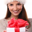Girl smiling in christmas hat and holding gift — Stock Photo #17146147