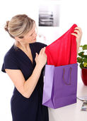 Mid age blonde woman checking shopping bags — Stock Photo