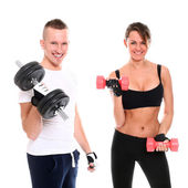 Young smiling couple lifting dumbbells in studio — Stock Photo