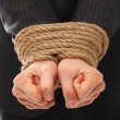 Close up of businessman hands tied with rope - Stock Photo