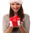 Cute girl smiling in christmas hat with a gift — Stock Photo