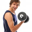 Handsome and sporty guy lifting dumbbell — Stock Photo