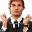 Handsome businessman hands in handcuffs - Stock Photo
