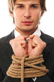Handsome businessman hands tied with rope — Stock Photo