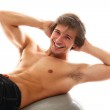 Handsome and sporty guy doing exercise for press — Stock Photo