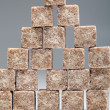 Brown sugar cubes stacked up on grey background — Stock Photo