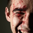 Close up of laughing man face in blood - Stock Photo