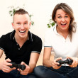 Young couple emotionally play video games at home - Stock Photo