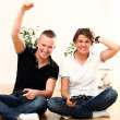 Young couple emotionally play video games at home — Stock Photo #17463905