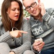 Young couple listen music in headphones at home - Stock Photo