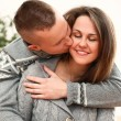 Happy couple embracing with kisses at home - Stock Photo
