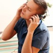 Young guy with headphones enjoying music at home — Stock Photo #17464157