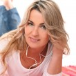 Mid aged woman listening music with headphones — Stock Photo