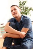Portrait of handsome young man thinking at home — Stock Photo