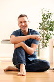 Portrait of handsome young man smiling at home — Stock Photo