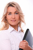 Woman in office suit smiling with laptop in hands — Stock Photo