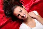 Beautiful and young brunette face lying on red — Stock Photo