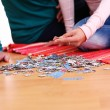 Granny and granddaughter playing puzzle - Stock Photo