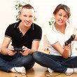 Young couple emotionally playing video games - Stock Photo