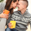 Couple embracing and kissing with cups in hands — Stock Photo