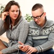 Young couple listening music in headphones — Stock Photo