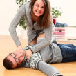 Angry woman choking a man lying on a floor — Stock Photo